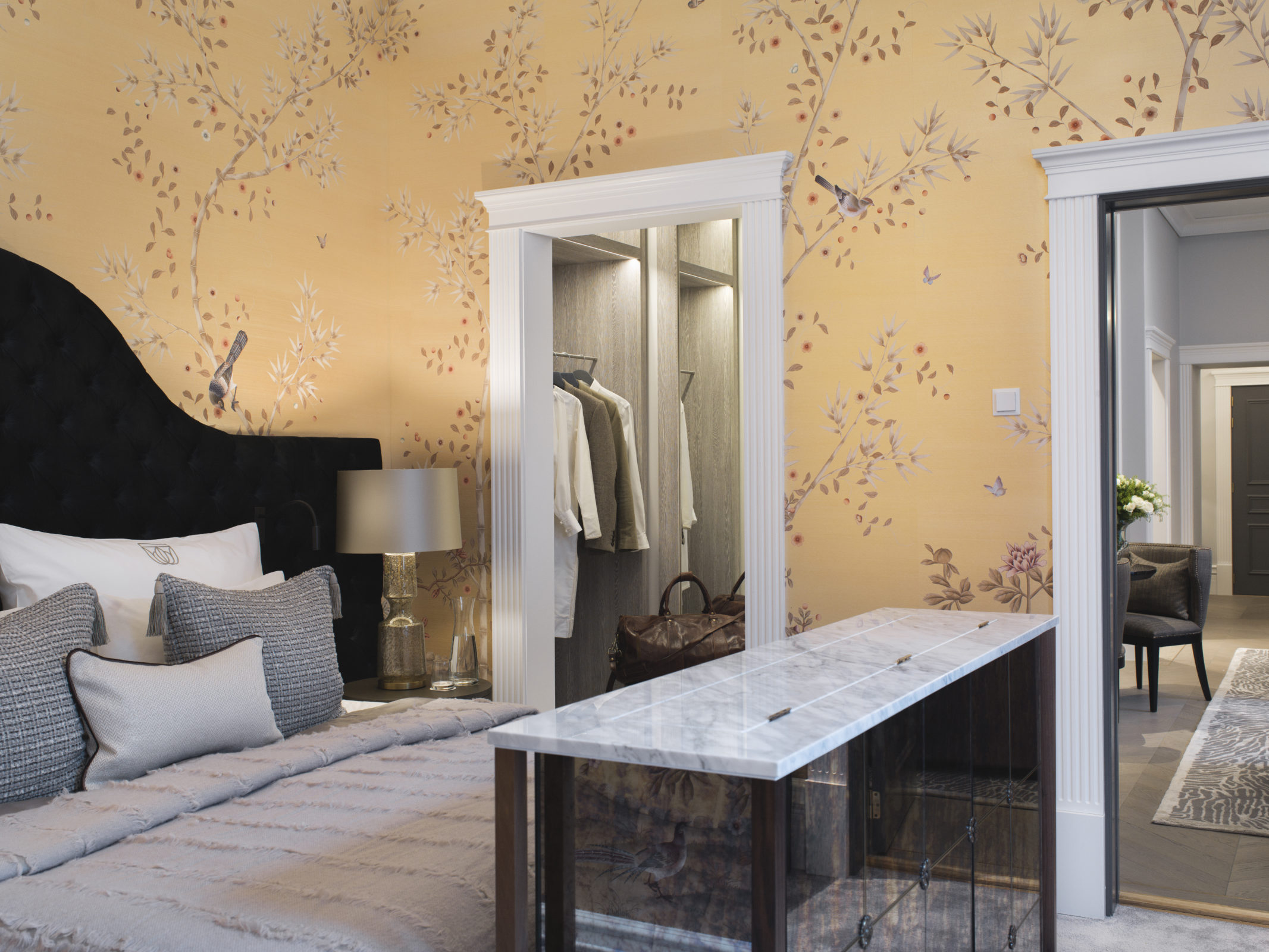 Britannia Hotel in Trondheim's Signature Suite styled by Metropolis Interior Architects. Detail of bed and walk wardrobe behind, with marble topped retractable TV in the foreground. Bed by Hästens.