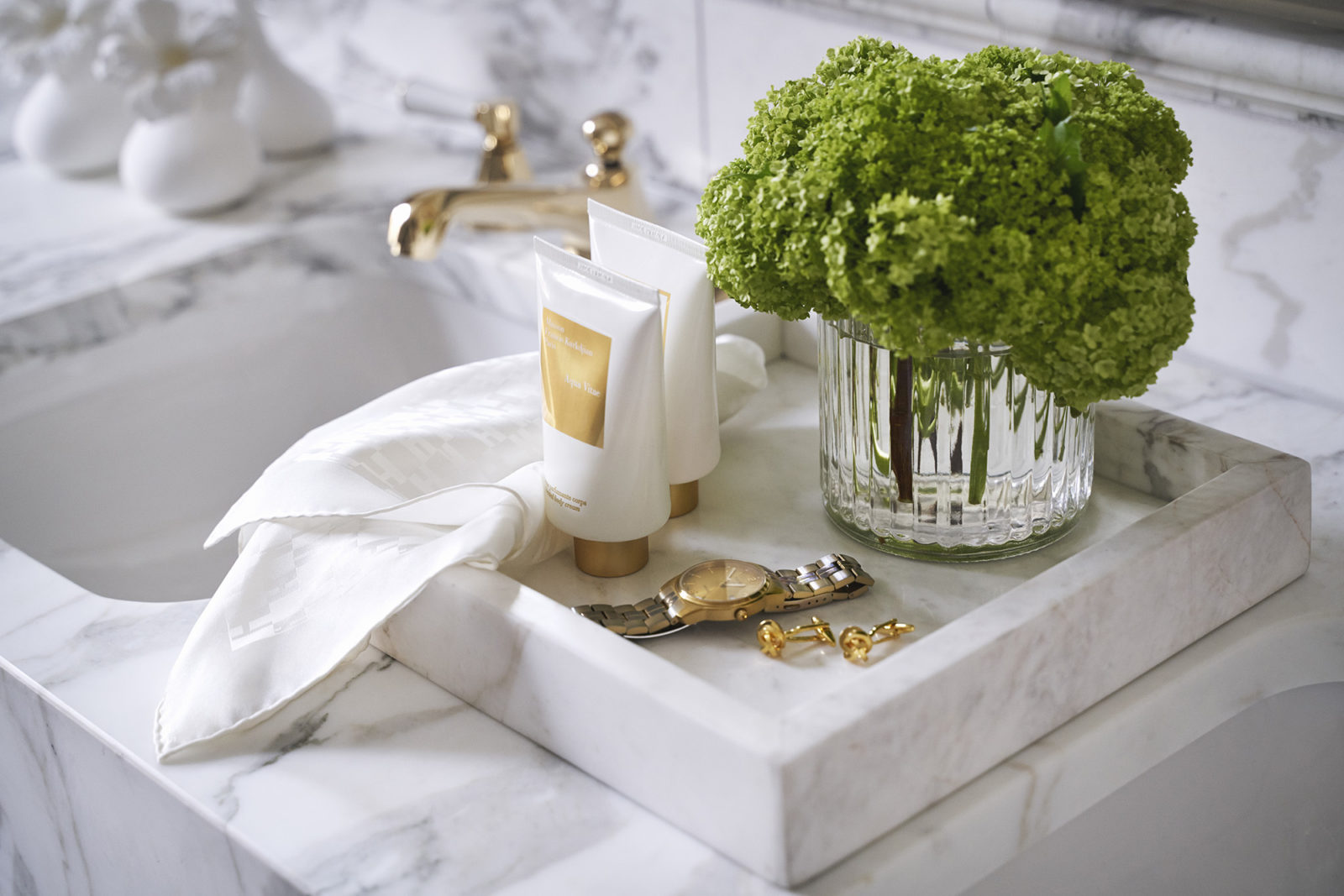 gold watch, cufflinks and toiletries in marble bathroom of Britannia Hotel's signature suite