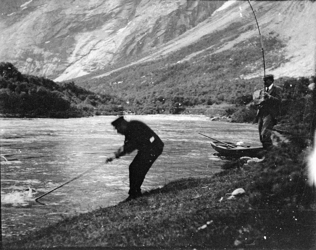 Peder Aak netting a salmon for William Bromsley-Davenport, one of the original Salmon Lords, at Langhølen on the Gaula river, around the turn of the 19th century.