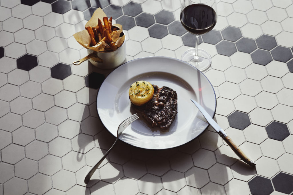 Photo of Entrecôte steak and chips, served at Brasserie Britannia, pictured on tiled floor.