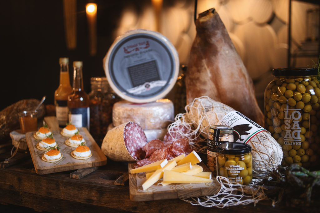 A display of hams, cheeses, blinis, olives and other deli items, as found in the Weekend pack at Vinbaren's Delicatessen, located at Britannia Hotel in Trondheim, Norway.