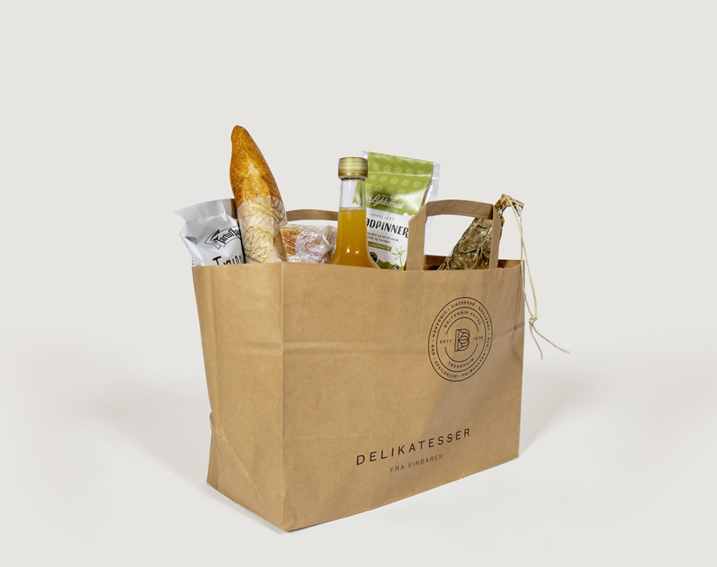 Paper bag with products fromVinbaren's Delian logo on outside, on white background