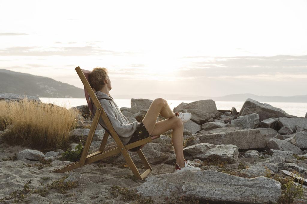 man on deckchair on Munkholmen island in Trondheim Fjord