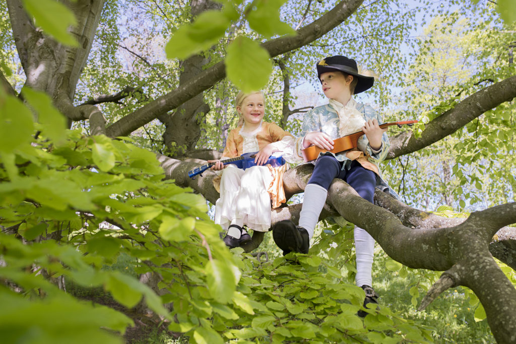 two kids playing an instrument in a tree at Ringve Music Museum