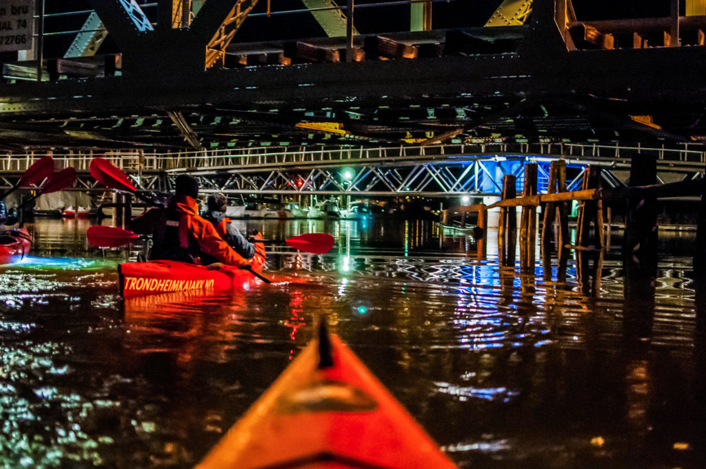 Kayak lit up with neon lights at night in. Trondheim