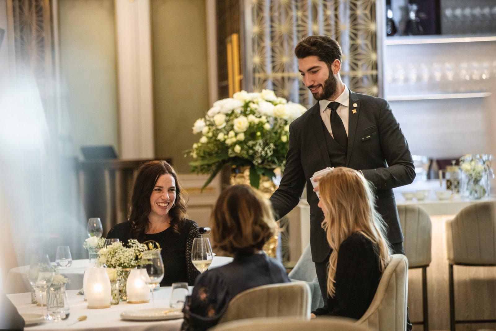 Servitør sjenker vin - Speilsalen restaurant