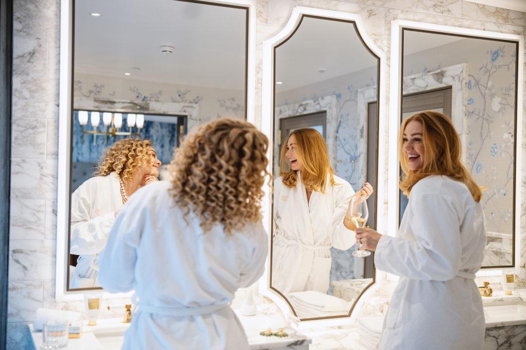 Friends getting ready in marble bathroom at Britannia Hotel